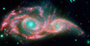 These shape-shifting galaxies have taken on the form of a giant mask. The icy blue eyes are actually the cores of two merging galaxies, called NGC 2207 and IC 2163, and the mask is their spiral arms. The false-colored image consists of infrared data from NASA's Spitzer Space Telescope (red) and visible data from NASA's Hubble Space Telescope (blue/green). 